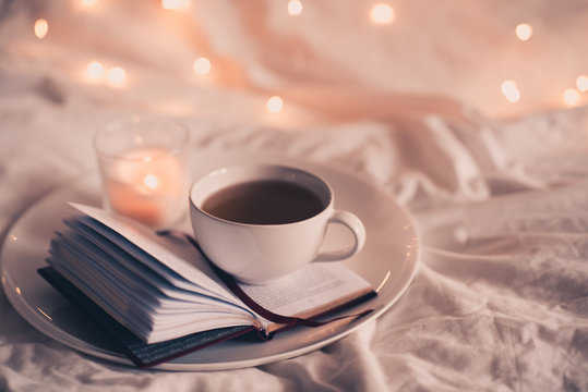 Cup of coffee with open book in bed over lights closeup. Good night.
