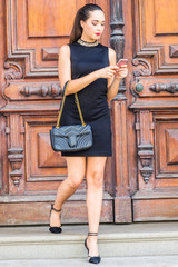Young South American Businesswoman working in New York City, wearing black sleeveless dress, arm carrying leather bag, walking dow stairs by brown vintage wooden office door, texting on cell phone.