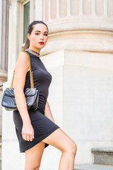 Go to Work. Young South American Businesswoman working in New York City, wearing black sleeveless dress, shoulder carrying leather bag, walking up stairs, going to office building, looking away..