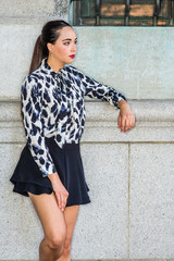 Young American Woman Street Fashion in New York City. South American College Student with ponytail hairstyle, wearing long sleeve patterned shirt, black short skirt, standing against wall on campus.