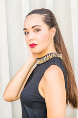 Portrait of South American Female College Student in New York City. Young Beautiful Hispanic Woman wearing black sleeveless dress, standing by column outside office building. Close Up Head Shot.