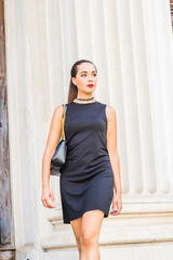 Go to Work. Young South American Businesswoman working in New York City, wearing black sleeveless dress, shoulder carrying leather bag, walking pass by column in office building, looking away..