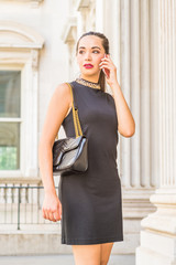 Young South American Businesswoman working in New York City, wearing black sleeveless dress, shoulder carrying leather bag, standing inside old style of vintage office building, talking on cell phone.