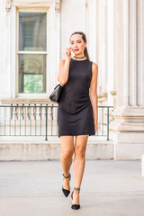 Go to Work. Young South American Businesswoman working in New York City, wearing black sleeveless dress, shoulder carrying leather bag, walking inside vintage office building, talking on cell phone..