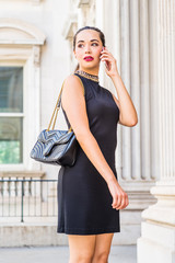 Go to Work. Young South American Businesswoman working in New York City, wearing black sleeveless dress, shoulder carrying leather bag, standing inside vintage office building, talking on cell phone.