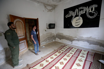 YPG is written over a wall painting of ISIS flag inside a house