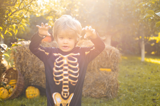 Halloween skeleton child. Halloween Kids Costume Party. Happy laughing child in costume to halloween. Funny kid in carnival costumes.