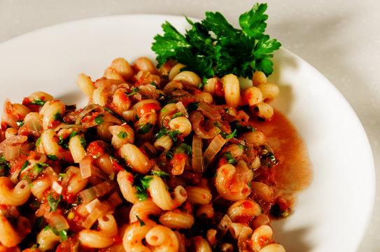 Healthy homemade mediterranean dish: pasta with marinara sauce and parsley. Closeup