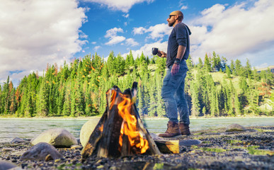 Man Standing With Coffee In Outdoor Mountain River Scene
