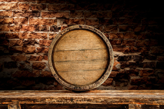 Old wooden wine barrelwith table board and brick wall background.