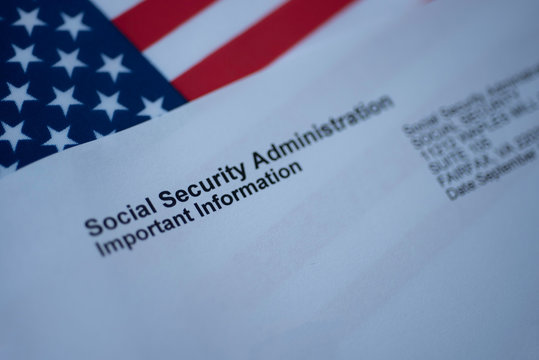 Social Security Administration Important Information letter next to flag of USA.