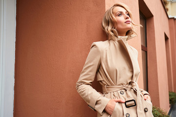 Beautiful stylish blond girl in trench coat dreamily looking away outdoor