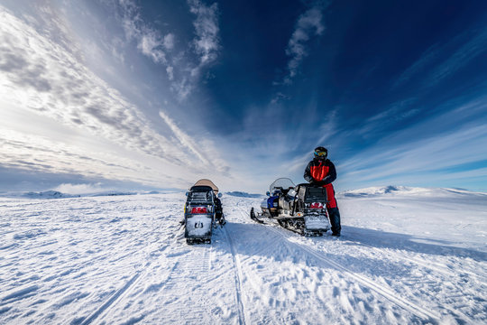 Two blue snowmobiles (back side) with a boy dressed for winter driving in cold mountains, he waits for his friend to continue the holiday adventure. Hemavan -Tarnaby area in Lappland, Sweden