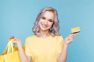 Image of happy girl holding credit card and big shopping bags isoleted over the blue studio