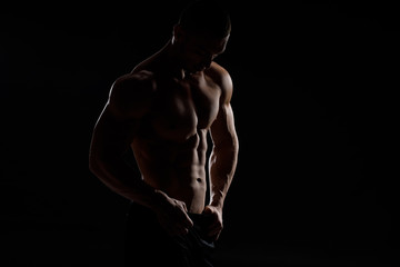 Muscular model sports young man in jeans showing his press on a black background. Fashion portrait of sporty healthy strong muscle guy. Sexy torso.