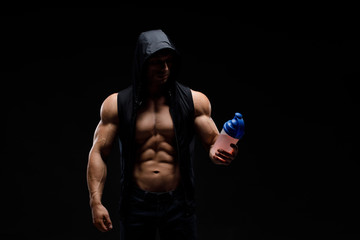 Model sports young man on dark background. Portrait of sporty strong muscle guy with protein drink in shaker. Sexy torso. Bodybuilding nutrition supplements, sport, workout, healthy lifestyle concept. Wall mural