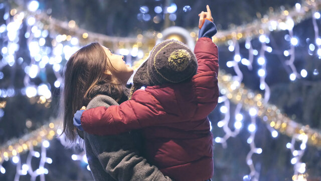 Portrait of mother holding child in her arms and admiring Christmas tree outdoor