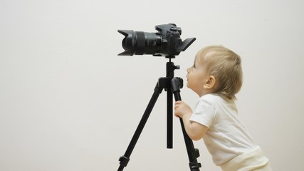 Funny baby child looking on photo camera scree on tripod, determined to work