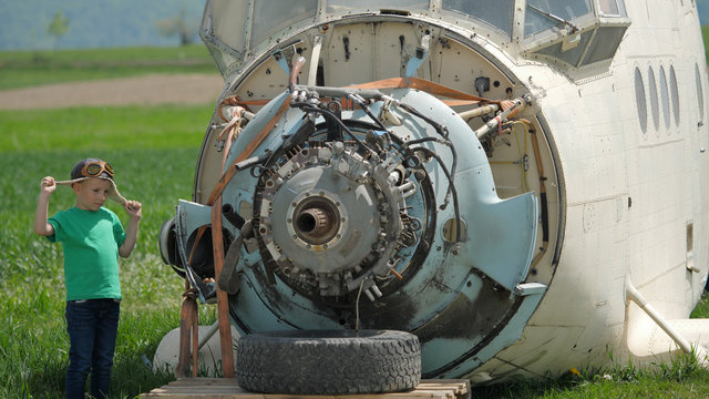 Funny child with pilot helmet looking at plane engine, difficult job