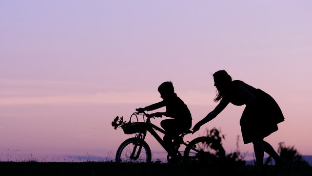 Mother and son silhouette at sunset, parent help child to learn to ride bike