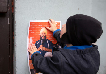 Four-year-old Felix Soucy pins up poster of NDP leader Jagmeet Singh outside election campaign rally venue in Montreal