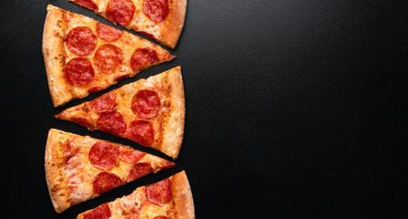 Pepperoni pizza slice on black slate background. Banner. Copy space. Pizza restaurant menu