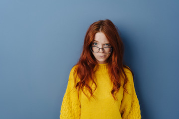 Dubious young woman with glasses lowered