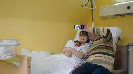 Family with newborn in hospital, father taking pictures, first memories