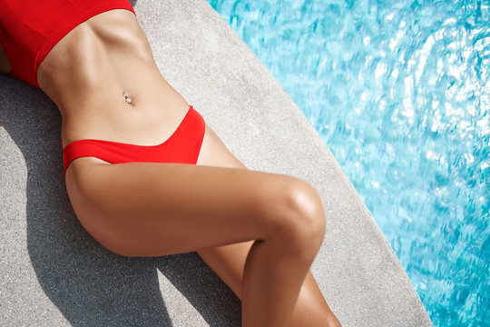 Enjoying vacation. Slim young woman with beautiful belly in red bikini swimwear near swimming pool.