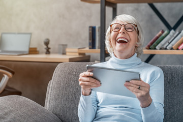 Happy senior woman looking and laughing at her digital tablet on sofa
