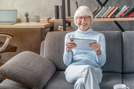 Portrait of smiling mature woman using digital tablet on sofa at home