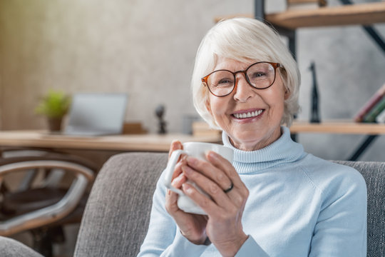 Senior woman drinking hot drink sitting on sofa at home