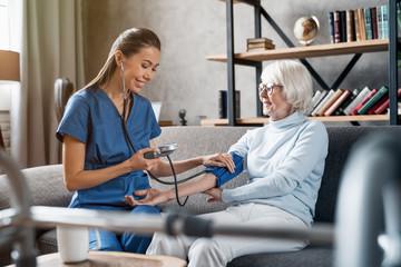 Nurse measuring blood pressure of elderly woman indoors