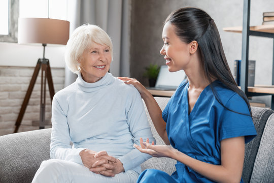 Nurse assisting with elderly woman at home