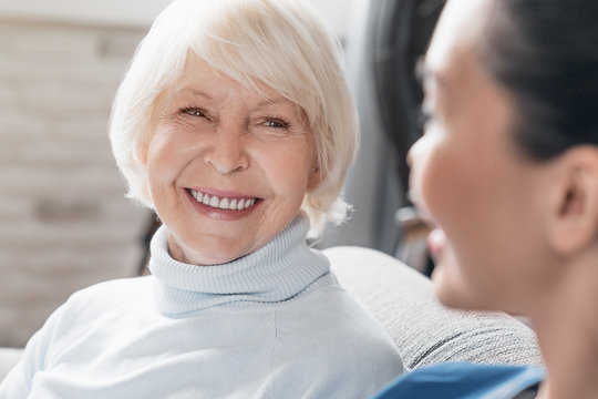 Close up of caregiver smiling and talking to aged woman while taking care of her at home