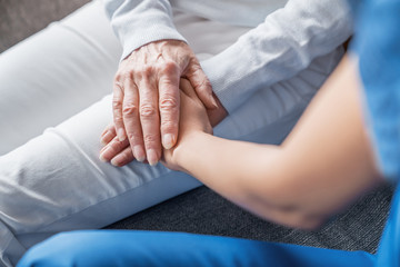Close up image of caregiver holding hands of elderly patient during home visit