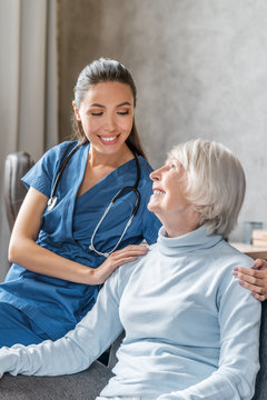 Vertical portrait of happy elderly woman with nurse at home