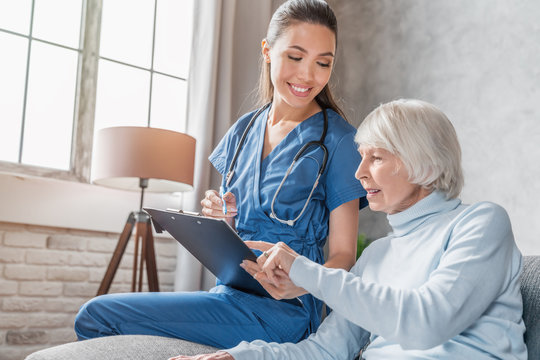 Smiling senior woman reading medical tests results in hands of nurse visiting her