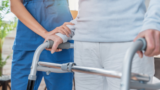Cropped image of nurse helping senior woman to walk with walker at home