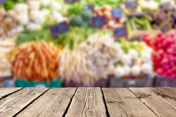 Blurred fresh vegetables at market with empty rustic wooden planks on the foreground. Can be used for advertise products. Mockup image.