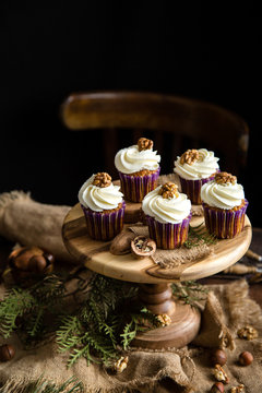 homemade carrot or pumpkin cupcakes with white cream and walnut on top