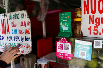 Mobile e-payment logos are seen at a street food stall in Ho Chi Minh city in Vietnam