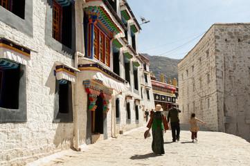 A small family walks along an alley at Deprung Monastery.