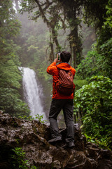 Hiker takes picture of Costa Rican Waterfall