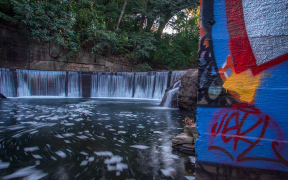 A Wall of Graffiti Next to a Man-Made Waterfall on a River - in a Secluded Spot in the City, Surrounded by Lush Green Trees