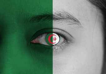 Human face painted Algeria flag with a red star and crescent on the center of eye or eyeball.