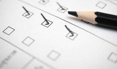 Black marking on checklist box with pencil close up. Checklist concept