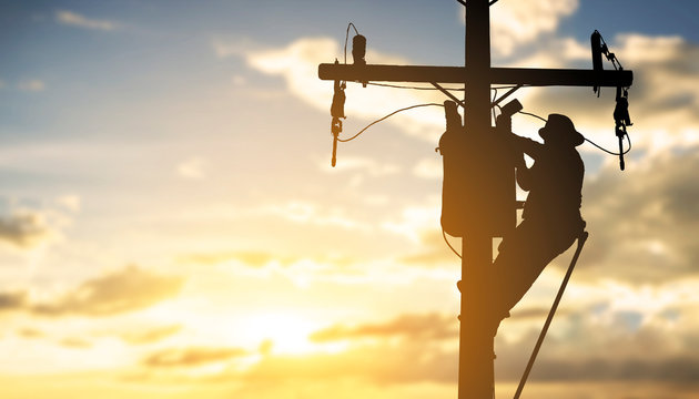 silhouette engineer working maintenance transformer on pole electric