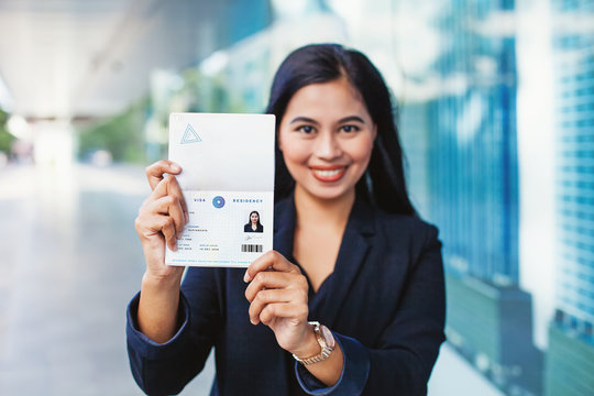 Asian woman showing valid visa and work permit in her passport