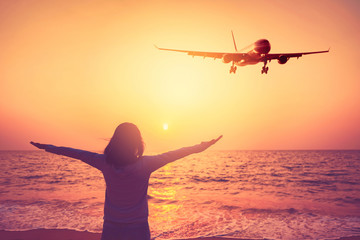 Airplane flying over woman rise hand up on sunset sky at beach and island background. Freedom travel adventure and transportation business concept.